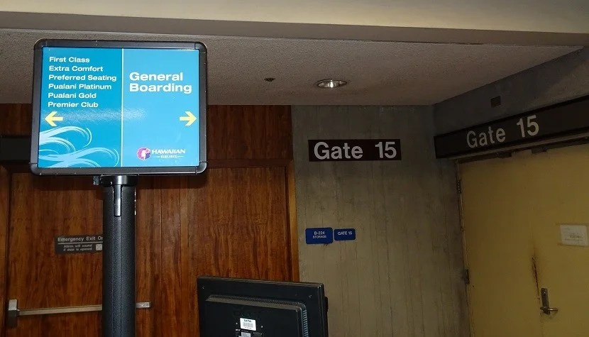 The wear and tear of Gate 15 shows behind the boarding sign.