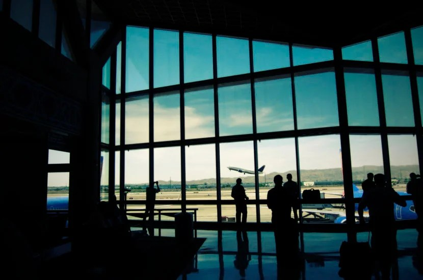 Inside Terminal D of passengers and airliner taking off at Phoenix Sky Harbor Airport.
