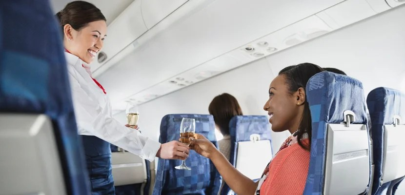 A woman having a glass of wine on an airplane. Image courtesy of Hero Images via Getty Images.