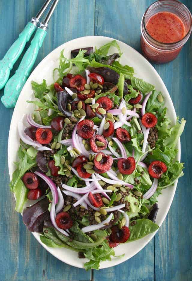 A healthy and antioxidant filled summer green salad. Cherries, black lentils, red onions, and pepitas make this a colorful and healthy salad! #greens #lentils #cherries