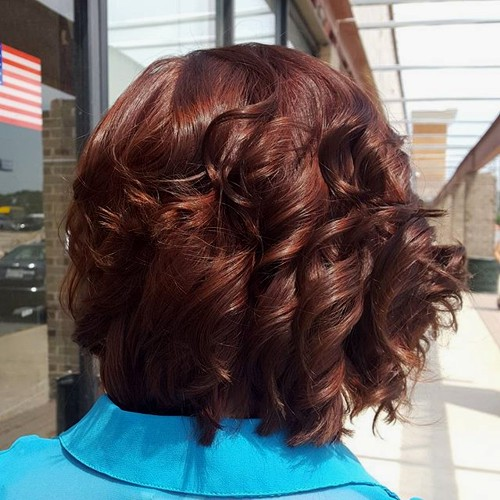 shorter reddish brown curly hairstyle
