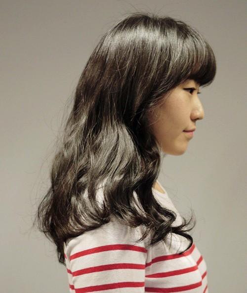 medium wavy hairstyle with full bangs