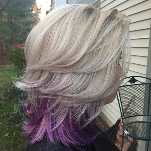 medium blonde layered hairstyle with lavender peek-a-boo highlights