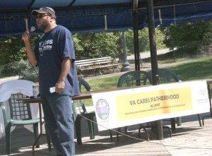 Correlli Rasheed speaks to a small crowd at Elmwood Park on Sunday.