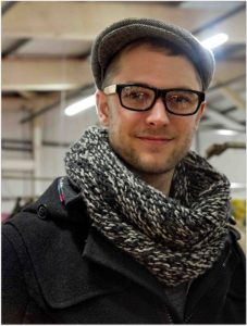Damien Leroy in a flat cap and black retro glasses.