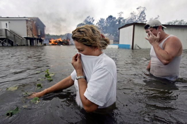 Rose Machado, left, walks in waist high floodwater as her neighbors' trailer burns in Lafitte, La., after Hurricane Rita passed through the area, Saturday, Sept. 24, 2005.  The person at right is not identified.  (AP Photo/Kevork Djansezian)