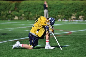Senior attacker Nick Trizano kneels down at the end of the Drexel men's lacrosse game versus Denver University in the quarterfinals of the NCAA Tournament. The Dragons lost, 15-6, to the Pioneers in what would prove to be Trizano's final game of his collegiate career. (Ken Chaney - The Triangle)