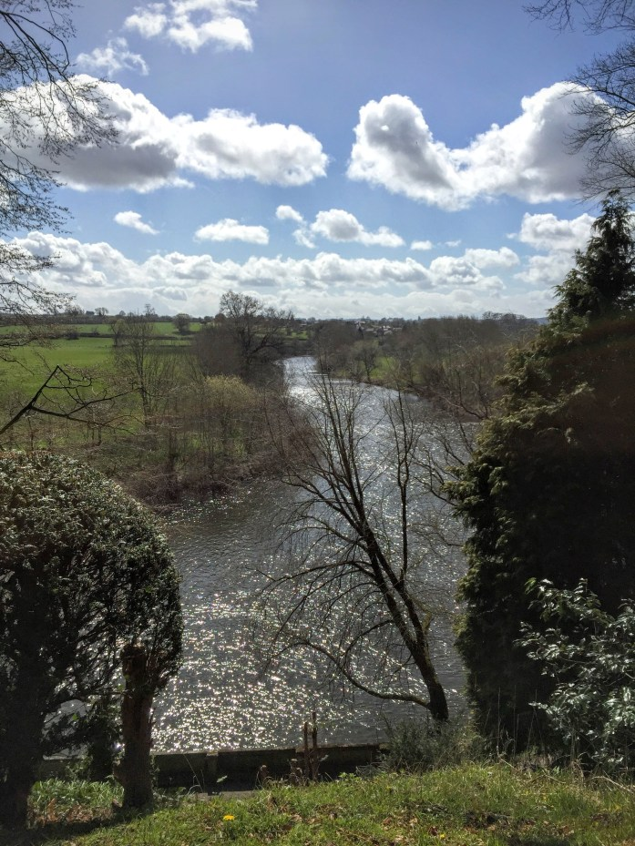The Weir Garden, National Trust, looking down onto the River Wye with fluffy white clouds and blue skies