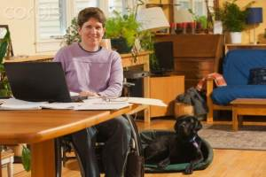 Women seated in a wheel chair at a desk in her home office.  A service dog is on the floor next to her.