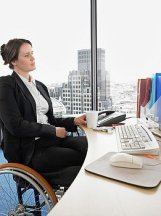 Business woman in a wheelchair sitting at a computer