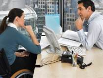 two office workers in meeting over a computer, one is in a wheelchair