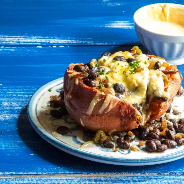 cheesy stuffed sweet potatoes with black beans, peppers, onion, and topped with creme fraiche.
