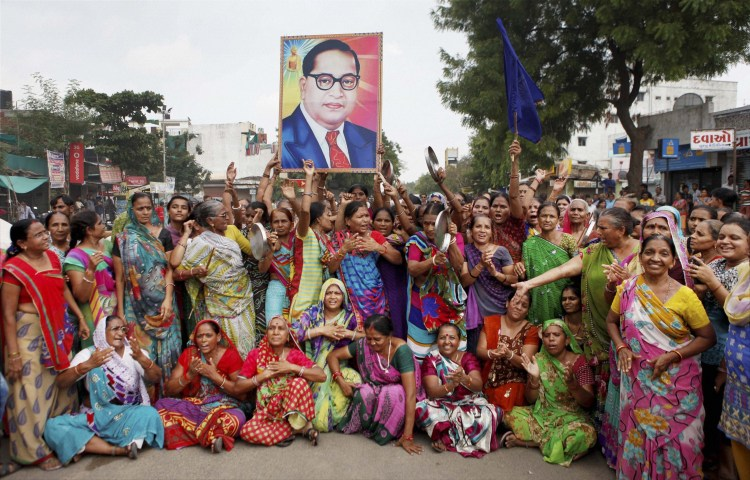 Dalit women carry a portrait of Ambedkar as they block traffic during a protest in Ahmedabad on Wednesday. Credit: PTI
