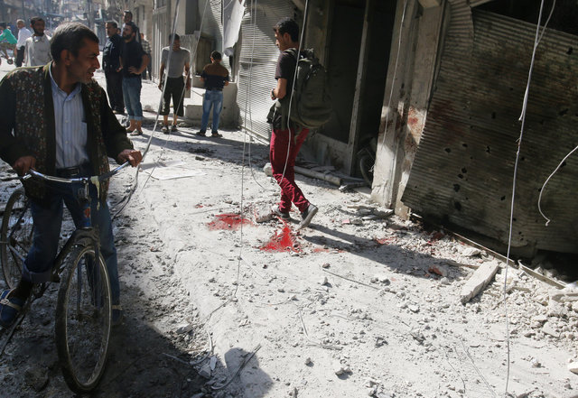 People inspect the damage as a civilian walks near bloodstains at a market hit by air strikes in Aleppo's rebel-held al-Fardous district, Syria October 12, 2016. REUTERS/Abdalrhman Ismail