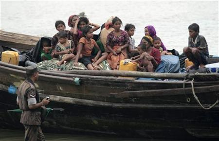 A member of the Border Guard of Bangladesh (BGB) inspects a boat carrying Rohingya refugees from Myanmar trying to get into Bangladesh in Teknaf June 13, 2012. REUTERS/Andrew Biraj
