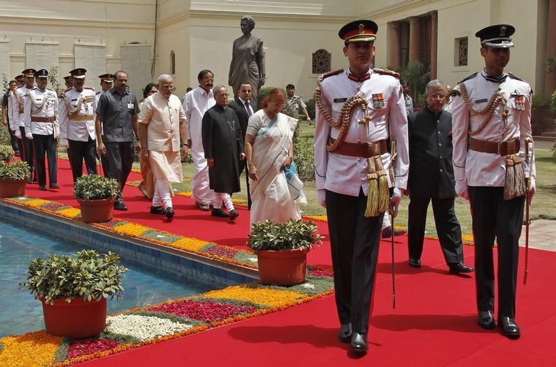 Indian President Pranab Mukherjee (C) arrives along with Prime Minister Narendra Modi (on his L) and Lok Sabha speaker Sumitra Mahajan (wearing sari), to address the joint session of the parliament in New Delhi June 9, 2014. Containing food inflation will be the top priority of Prime Minister Narendra Modi's new government, Mukherjee said in a parliamentary address on Monday, with an emphasis on improving supplies and farm pricing. REUTERS/Stringer (INDIA - Tags: POLITICS) - RTR3STTC