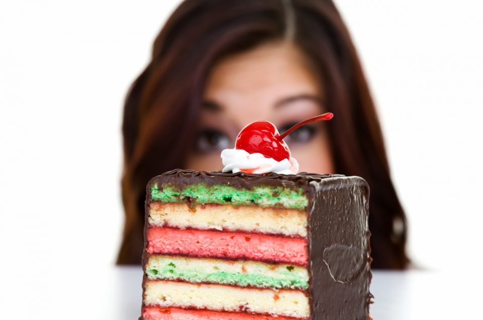 Closeup of a piece of cake with a woman in the background