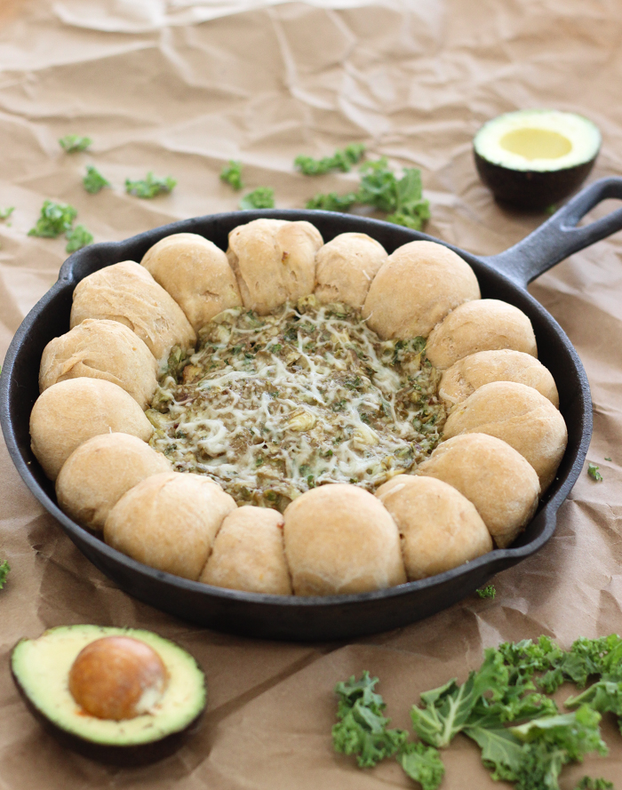 A healthy dip made with avocado, kale, artichokes, and greek yogurt along with homemade whole wheat garlic rolls!