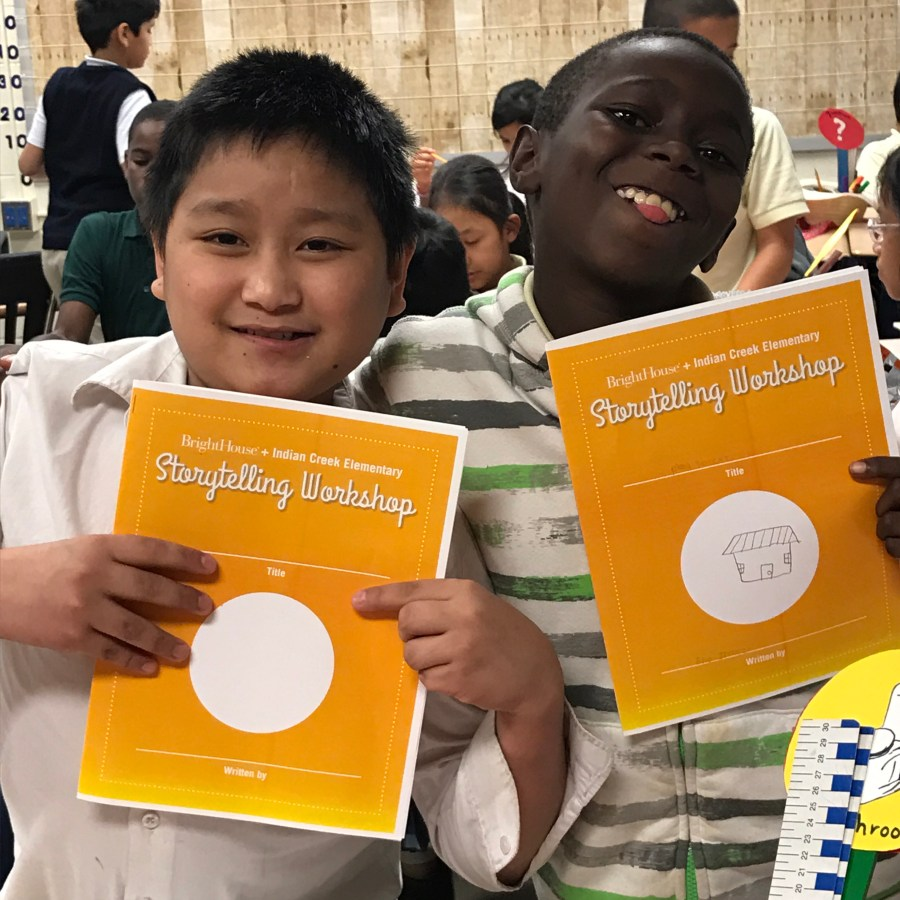 Two students with the storytelling booklet we designed