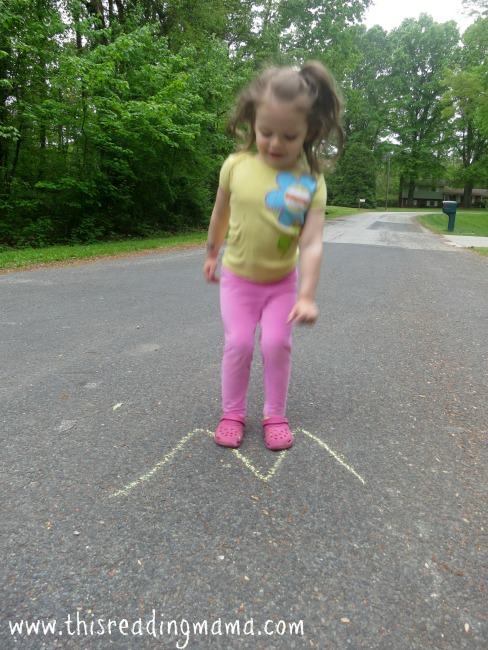 jumping on letters drawn with sidewalk chalk
