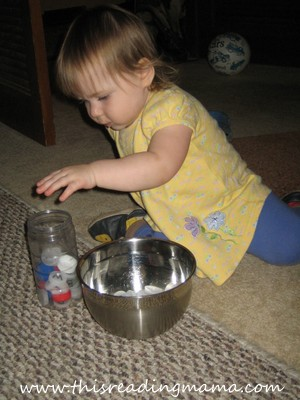 photo of toddler transferring bottle caps