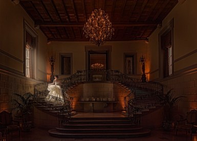 """Oheka Castle has such marvelous locations for wedding pictures. One of those locations is the stairwell in their main lobby. Featured in such places as Taylor Swift's """"Blank Space"""" video, the TV show Royal Pains, and movies such as Citizen Kane, Oheka's ornate lobby is a site to behold. Build nearly one hundred years ago by Otto Hermann Kahn, Oheka still remains the second biggest private home ever constructed in the United States. It boasts one hundred and twenty-seven rooms, over a hundred thousand square feet of space, and is one of my favorite locations to shoot wedding photographs! After being abandoned for years in the 1980's, Oheka was eventually purchased by Gary Melius, a developer. Under the careful instruction of historians and architects, every detail was meticulously rebuilt. It took two years. Oheka Castle can be found on the National Register of Historic Places. It is also one of the Historic Hotels of America. Many wedding clients love having their wedding pictures taken on the Grand Staircase at Oheka Castle. I can totally understand why! The ornate metal railings are truly beautiful. The split staircase is elegant in its' symmetry. The light that pours into the lobby from the two tall front doors is really gorgeous. Oheka's lobby has a quiet grace about it, and it's a great site for wedding portraits and photographs. We often create family portraits in this location. The middle landing is a great place to pose your bridal party, bridesmaids, groomsmen, and family formal portraits. This location makes for a great, iconic Oheka look to your formal wedding day portraits. At this particular wedding, we found ourselves in the lobby at exactly the right time! The light was streaming through the window to the left of the staircase in a way that I had never seen it do before. It was such a fleeting experience, as it was gone not ten minutes later! Everything that makes Oheka Castle so charming came together into one amazing bridal portrait, all at once. Th"""