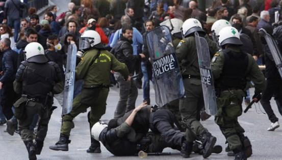 Greek riot policemen arrest a demonstrator during a protest in Athens