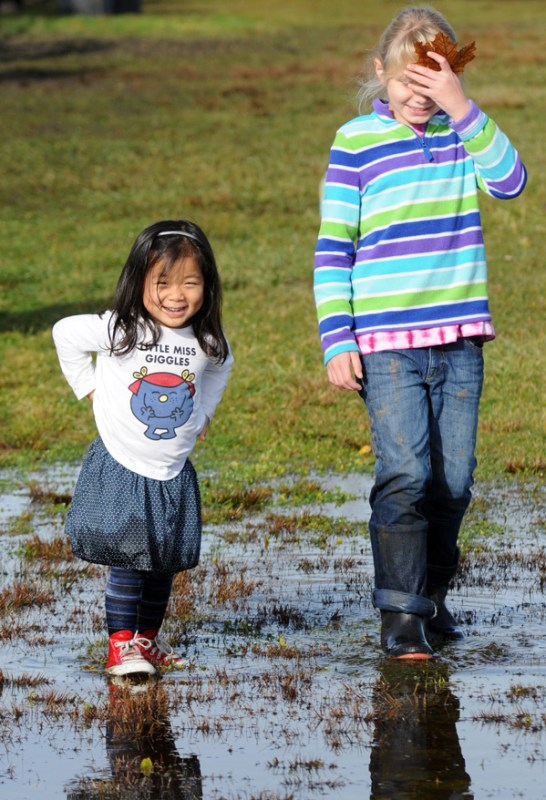Li Li had a great time playing with her new friend Macy in the large puddles.