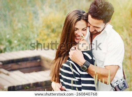 happy romantic couple in love and having fun with daisy at the lake outdoor in summer day, beauty of nature, harmony concept - stock photo
