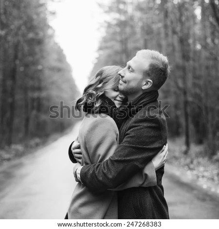 Outdoor vintage black and white fashion portrait of pretty young hipster couple in love posing in forest  - stock photo