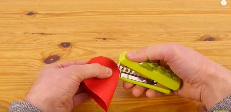 Stapling closed the back of the paper 3D heart.
