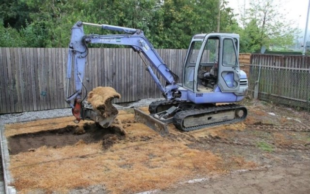 Blue backhoe beginning to dig pool that will look like a pond