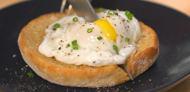 Close-up of cutting poached egg on toast