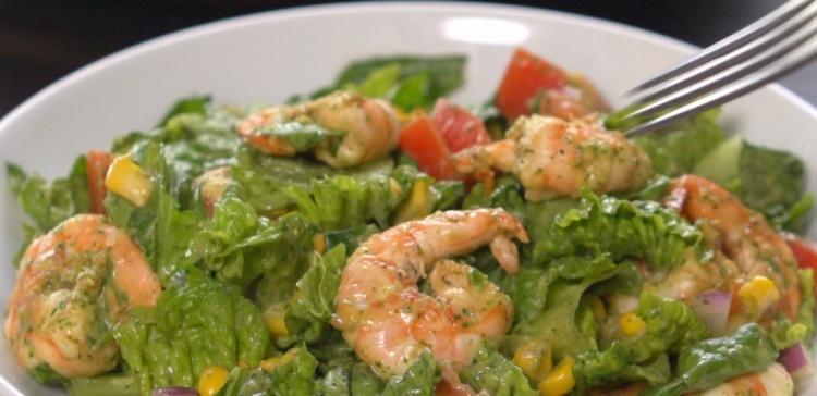 Close-up of fork piercing shrimp avocado salad