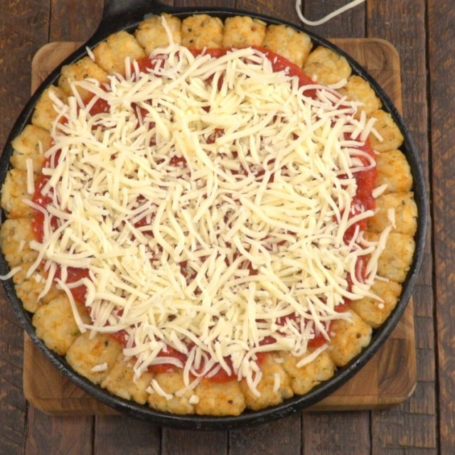 Top tater tot crust with pizza sauce and shredded mozzarella