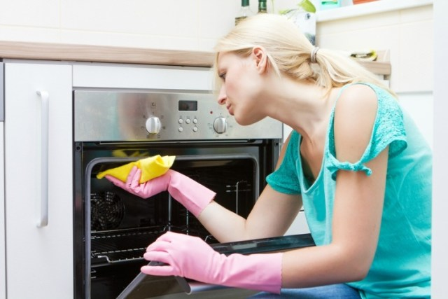 Blonde woman cleaning oven with yellow cloth