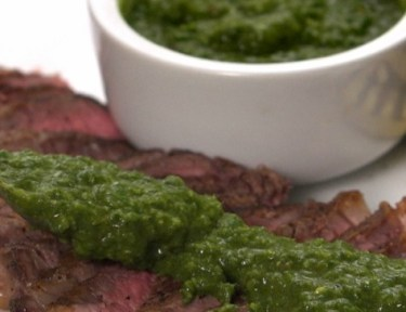 Close-up of spreading chimichurri sauce on steak