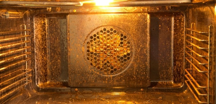 Inside of a really dirty oven needing cleaning