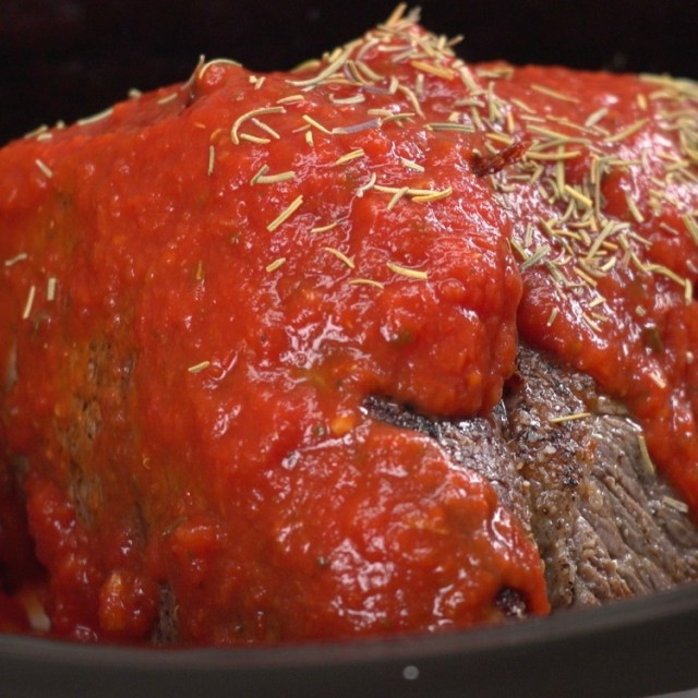 Marinara sauce poured of pot roast in slow cooker