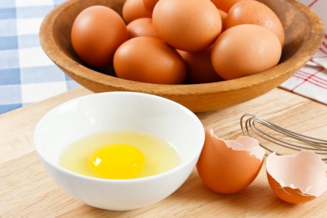 basket of brown eggs with raw egg