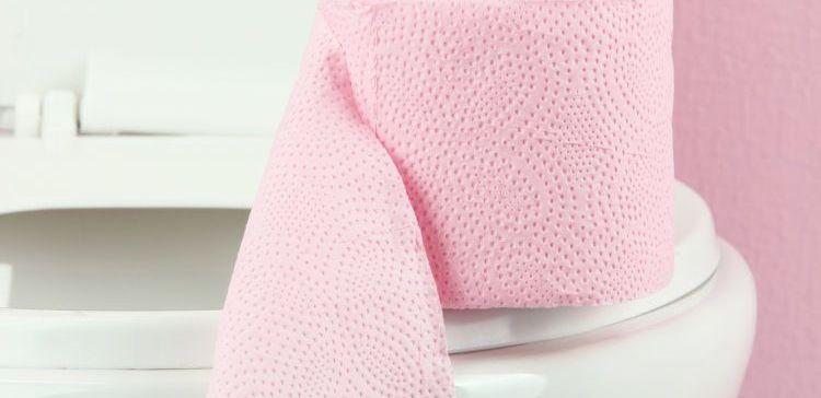 pink toilet paper on white toilet bowl