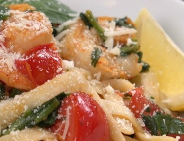Close-up of shrimp tomato and spinach pasta on white plate