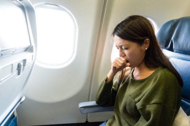 woman coughing on airplane