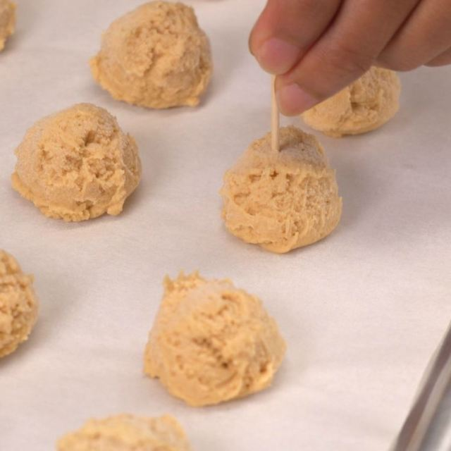 Balls of peanut butter cream cheese mixture being pierced with toothpick