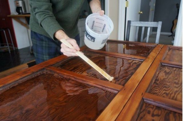 user pours epoxy on table