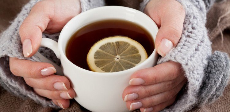 woman holds a cup of tea with lemon