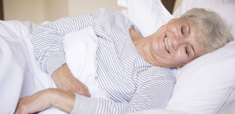 older woman smiling and sleeping