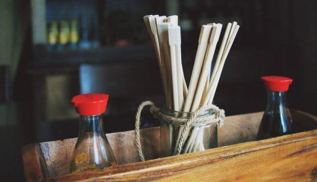 soy sauce bottles in basket with chopsticks