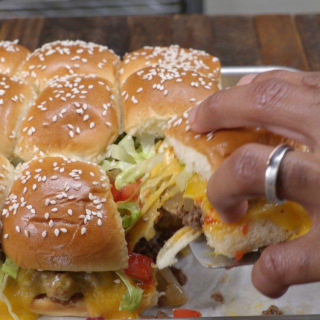 Pulling apart cheesy bacon slider from others