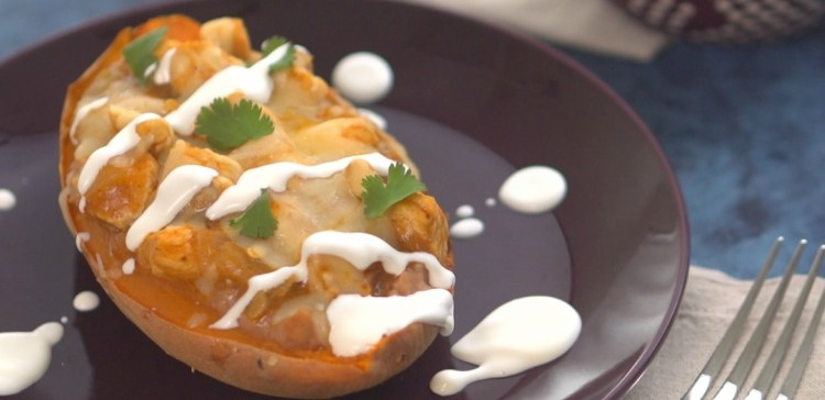 Close-up of enchilada loaded sweet potato on black plate